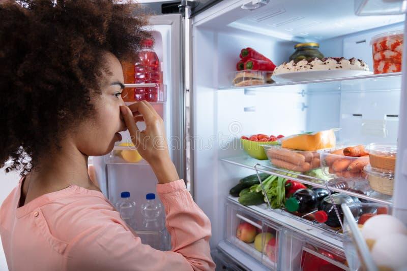 Mulher que reconhece o cheiro mau do refrigerador foto de stock