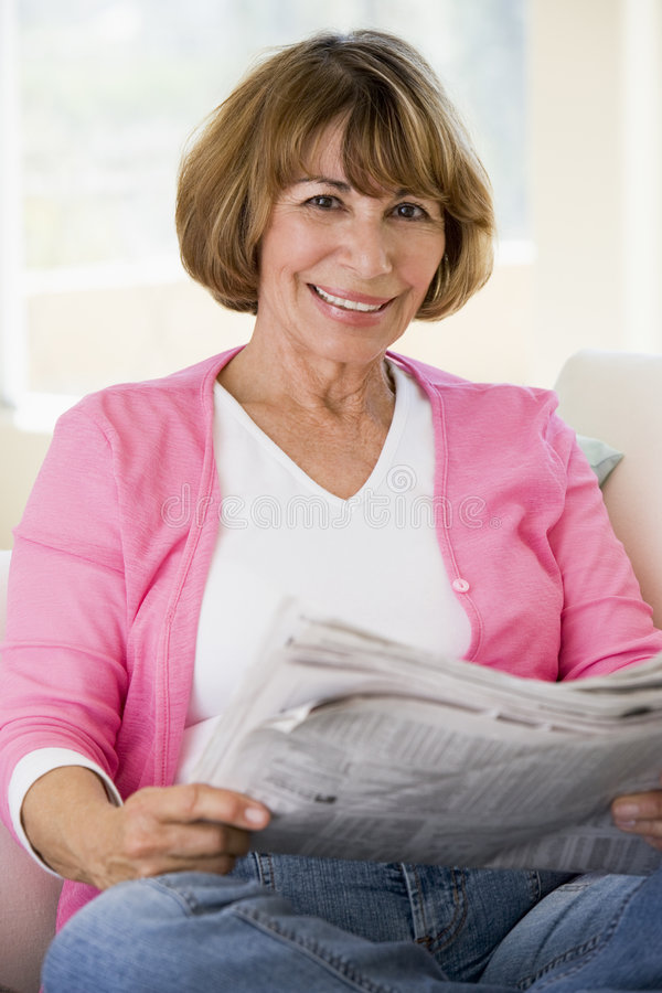 Mulher que relaxa com o jornal na sala de visitas imagem de stock