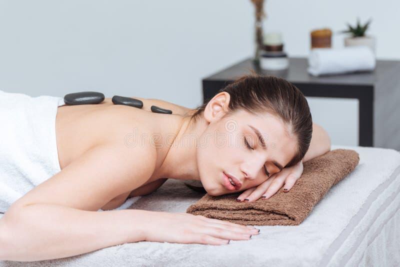 Mulher que relaxa e que recebe a massagem de pedra quente no salão de beleza dos termas foto de stock royalty free