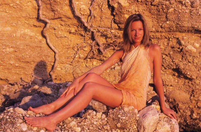 Mulher que relaxa em rochas foto de stock royalty free