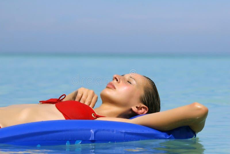 Mulher que relaxa em um colchão de ar foto de stock