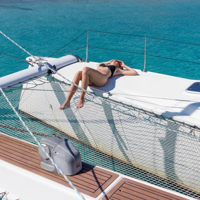 Mulher que relaxa em um cruzeiro da naviga??o do ver?o, assento em um catamar? luxuoso perto do Sandy Beach branco perfeito da im fotografia de stock