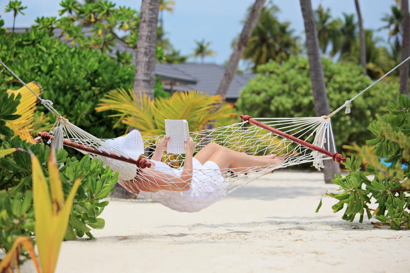 Mulher que relaxa em um hammock e que lê um livro em uma praia fotos de stock