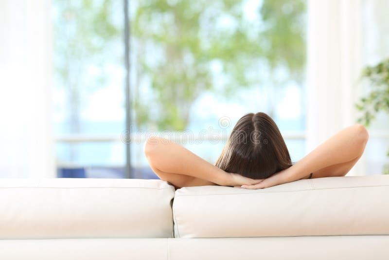 Mulher que relaxa em um sofá em casa fotografia de stock