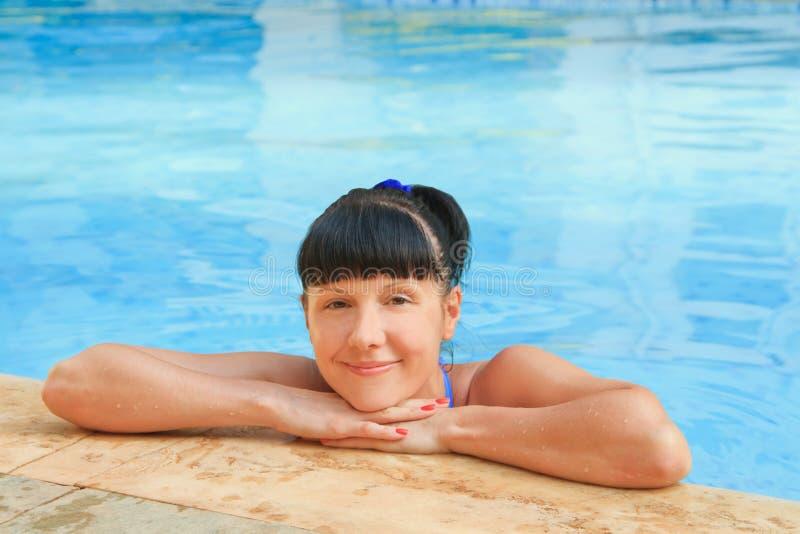 Mulher que relaxa em uma associação azul fotografia de stock royalty free