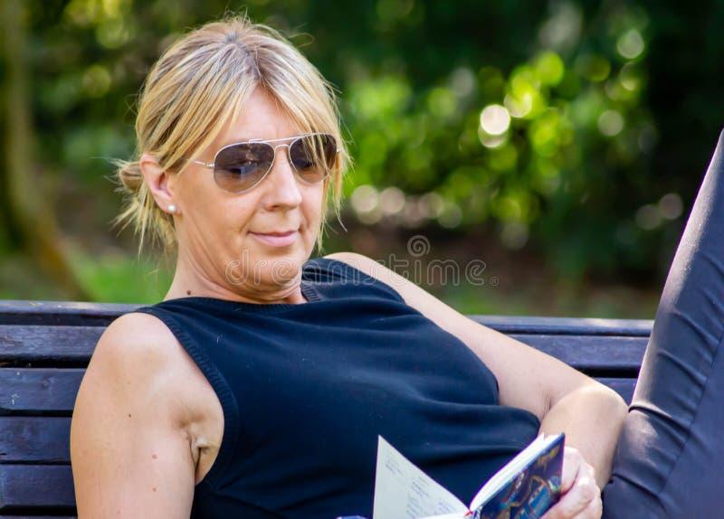 Mulher que relaxa em uma leitura do parque, louro maduro para muitos, a leitura é uma maneira de descansar do esforço, mas é igua foto de stock royalty free