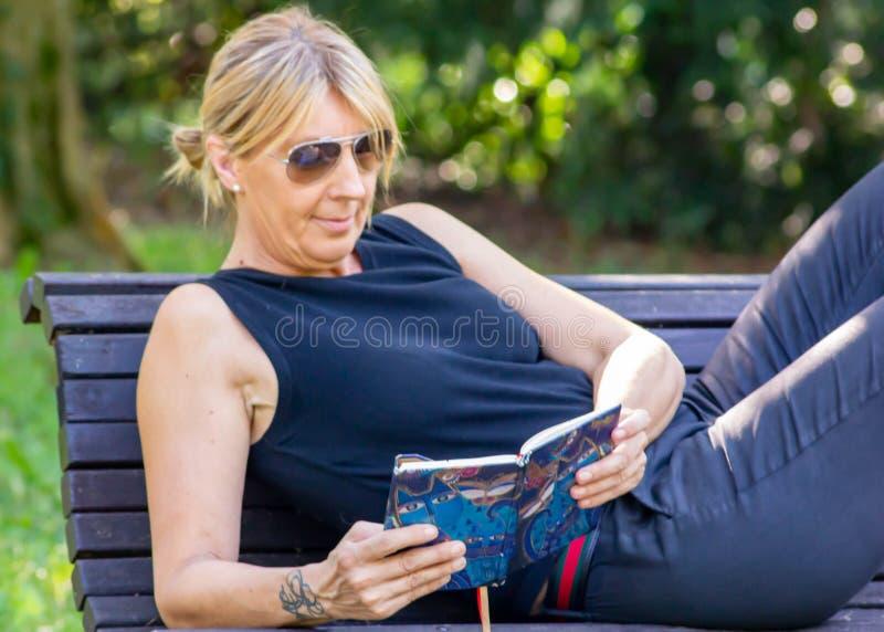 Mulher que relaxa em uma leitura do parque, louro maduro para muitos, a leitura é uma maneira de descansar do esforço, mas é igua imagem de stock