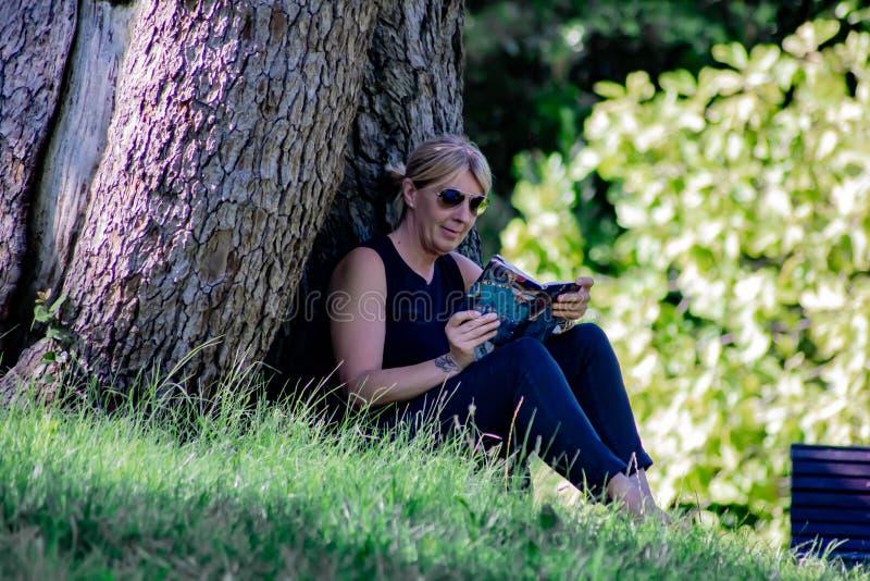 Mulher que relaxa em uma leitura do parque, louro maduro para muitos, a leitura é uma maneira de descansar do esforço, mas é igua fotografia de stock