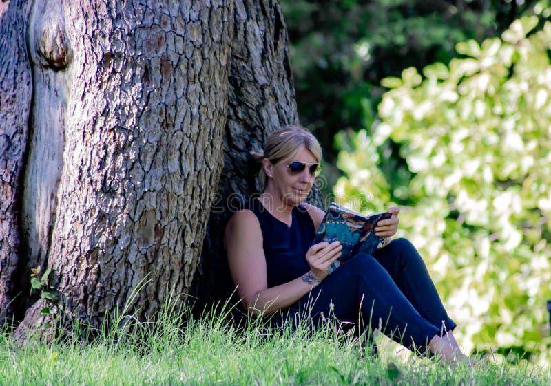 Mulher que relaxa em uma leitura do parque, louro maduro para muitos, a leitura é uma maneira de descansar do esforço, mas é igua fotos de stock royalty free