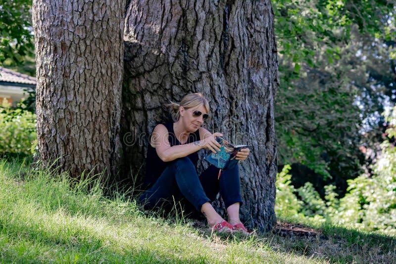 Mulher que relaxa em uma leitura do parque, louro maduro para muitos, a leitura é uma maneira de descansar do esforço, mas é igua foto de stock