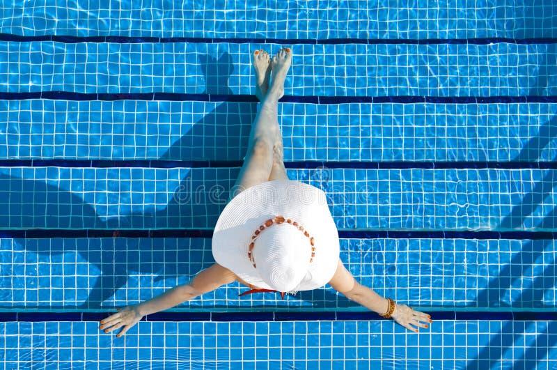 Mulher que relaxa em uma piscina do recurso imagem de stock