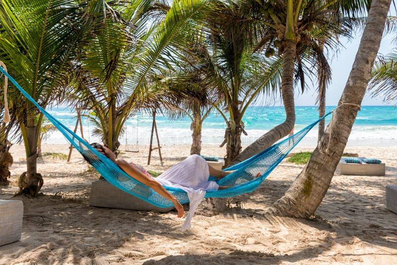 Mulher que relaxa em uma rede em uma praia tropical imagens de stock royalty free