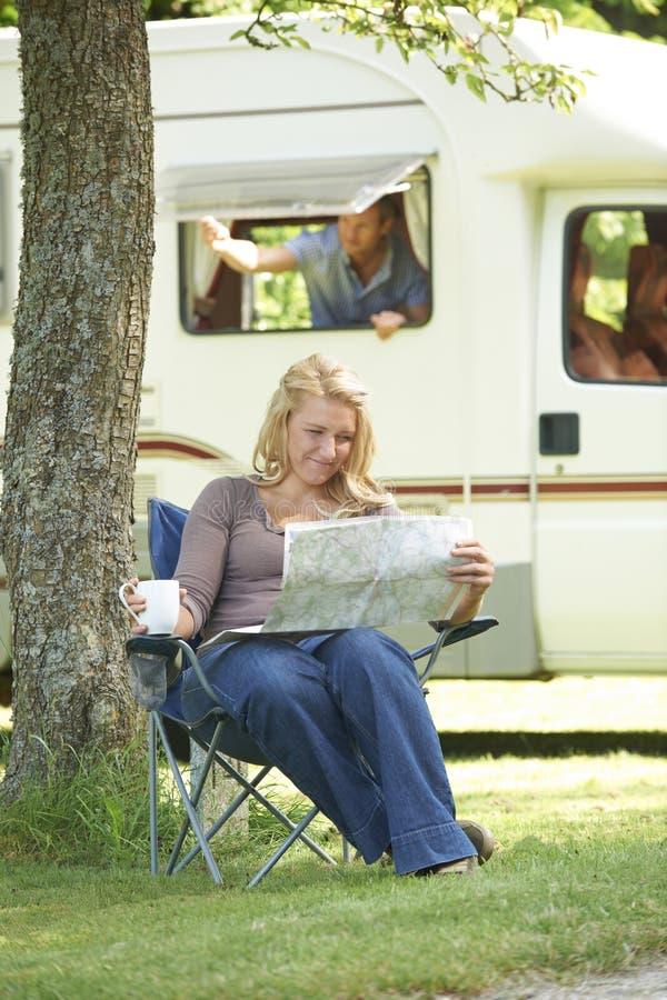 Mulher que relaxa fora da roulotte em férias fotos de stock
