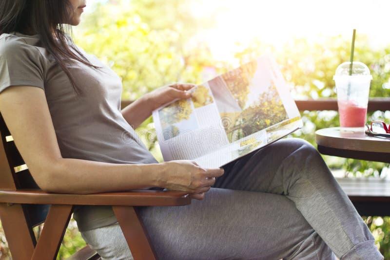 Mulher que relaxa lendo o batido de viagem do compartimento e da morango na tabela fotografia de stock