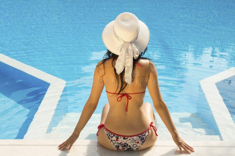 Mulher que relaxa na borda de uma piscina foto de stock