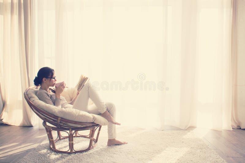 Mulher que relaxa na cadeira imagens de stock royalty free