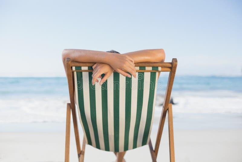 Mulher que relaxa na cadeira de plataforma na praia foto de stock royalty free