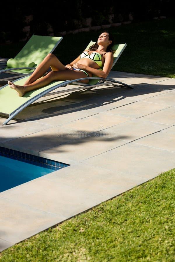 Mulher que relaxa na cadeira de sala de estar na piscina imagem de stock royalty free