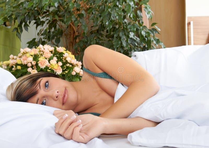 Mulher que relaxa na cama cosy foto de stock royalty free