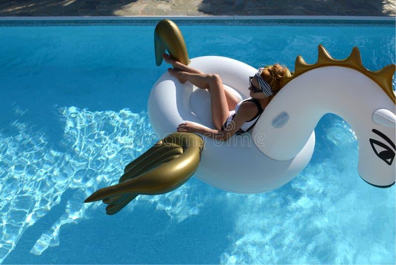 mulher que relaxa na estância luxuosa da piscina no unicórnio inflável grande que flutua o flutuador de pegasus fotografia de stock royalty free
