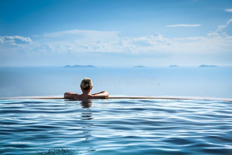 Mulher que relaxa na piscina da infinidade que olha a vista imagens de stock royalty free