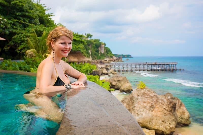 Mulher que relaxa na piscina em férias tropicais imagens de stock
