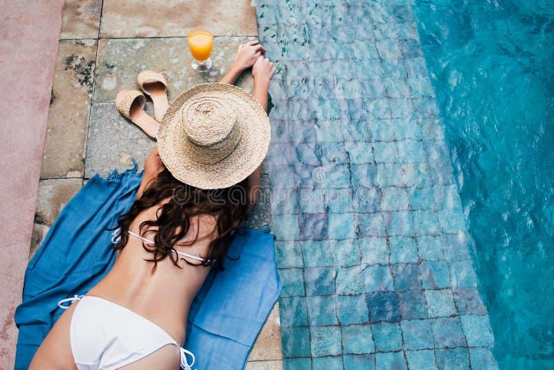 Mulher que relaxa na piscina fotos de stock royalty free