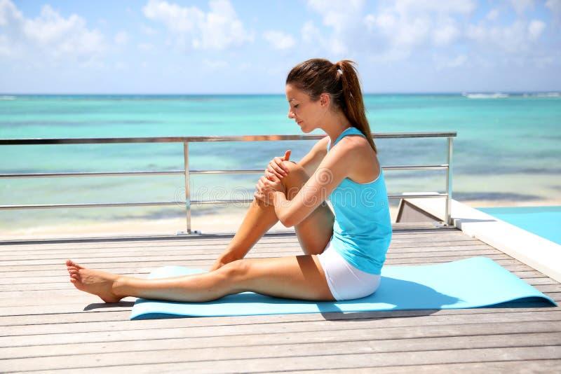Mulher que relaxa na plataforma de madeira após esportes fotos de stock