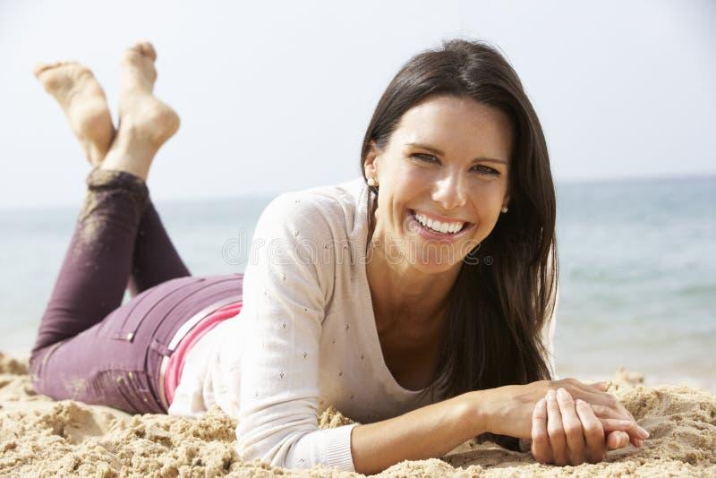 Mulher que relaxa na praia foto de stock