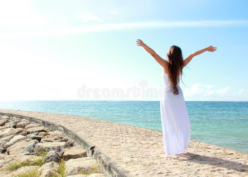 A mulher que relaxa na praia com braços abre a apreciação de sua liberdade foto de stock royalty free