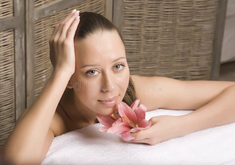 Mulher que relaxa na toalha no banheiro de madeira à moda com flores, cuidados com a pele orgânicos, hotel luxuoso dos termas, fo imagens de stock royalty free
