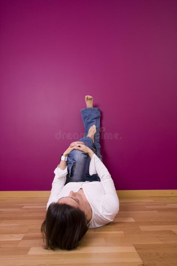 Mulher que relaxa no assoalho fotos de stock royalty free