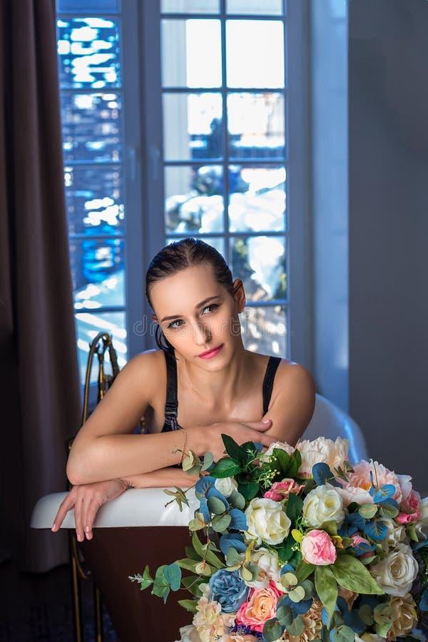 Mulher que relaxa no banho com flores, cuidados com a pele orgânicos, hotel luxuoso dos termas, foto do estilo de vida fotografia de stock