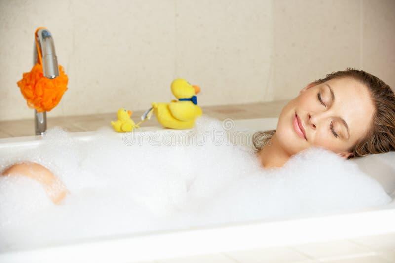 Mulher que relaxa no banho enchido bolha imagem de stock