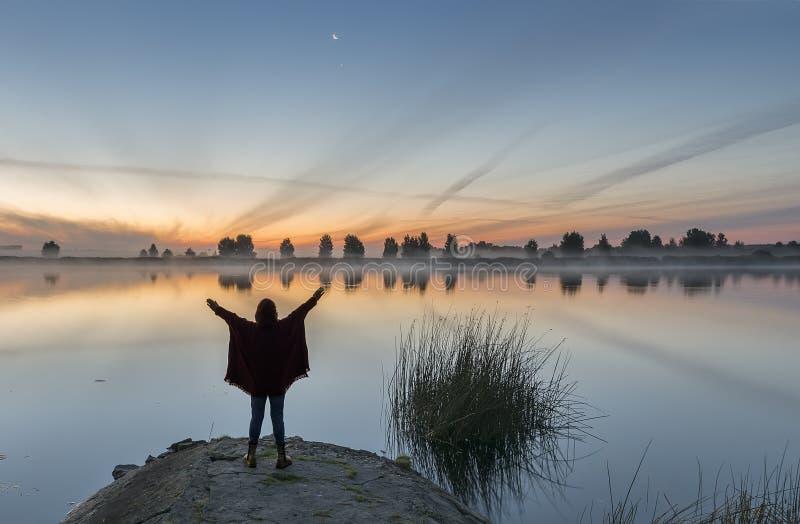 Mulher que relaxa no beira-rio antes do nascer do sol imagens de stock royalty free