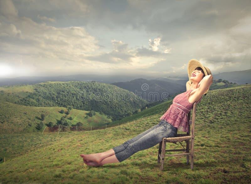 Mulher que relaxa no campo fotografia de stock