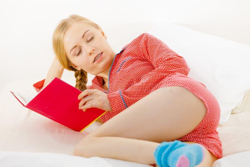 Mulher que relaxa no livro de leitura da cama foto de stock