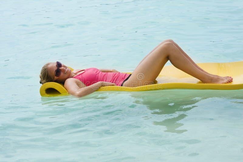 Mulher que relaxa no oceano imagem de stock