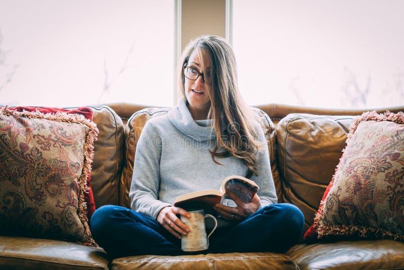 Mulher que relaxa no sofá fotografia de stock royalty free