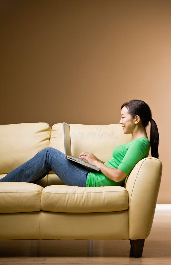 Mulher que relaxa no sofá na sala de visitas