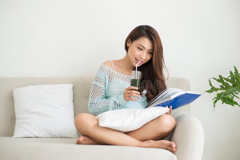 Mulher que relaxa no sofá na sala de visitas que aprecia lendo um livro e bebendo o café imagem de stock