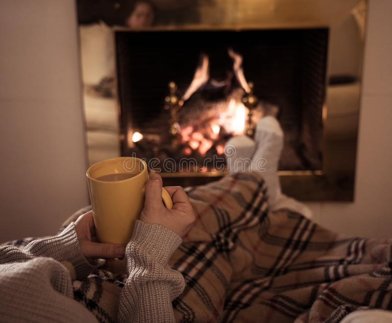 Mulher que relaxa pela chaminé que aquece os pés em de lã com um copo de peúgas e da cobertura quentes da bebida foto de stock royalty free