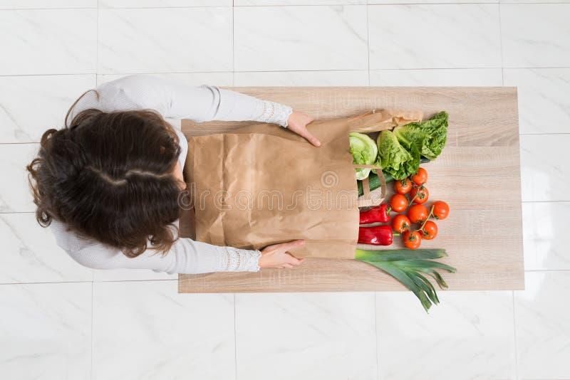 Mulher que remove os vegetais do saco de compras imagens de stock royalty free