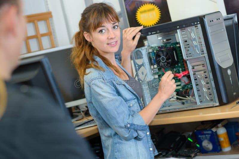 Mulher que repara o computador que gerencie para falar ao cliente imagens de stock