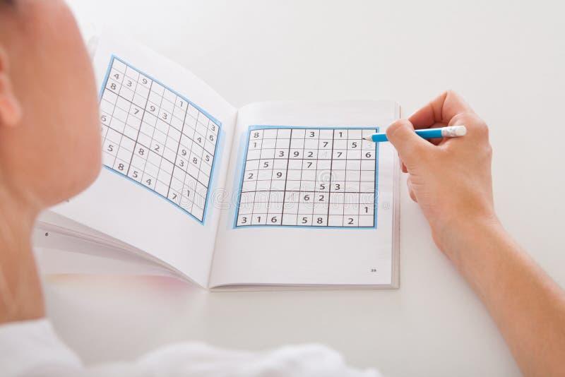Mulher que resolve Sudoku fotografia de stock