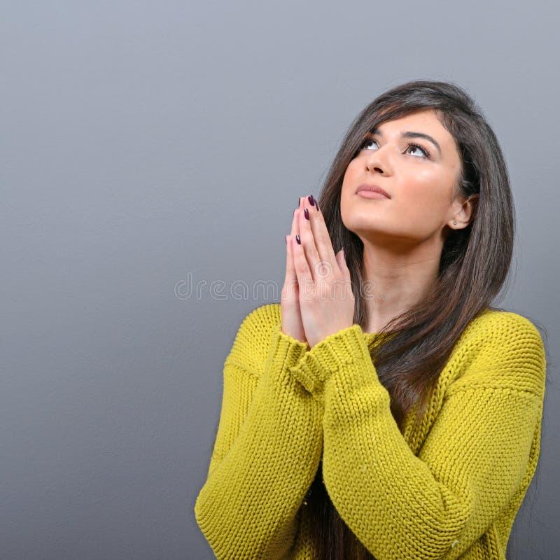 Mulher que reza sobre algo ou que implora pela mercê contra o fundo cinzento fotos de stock royalty free