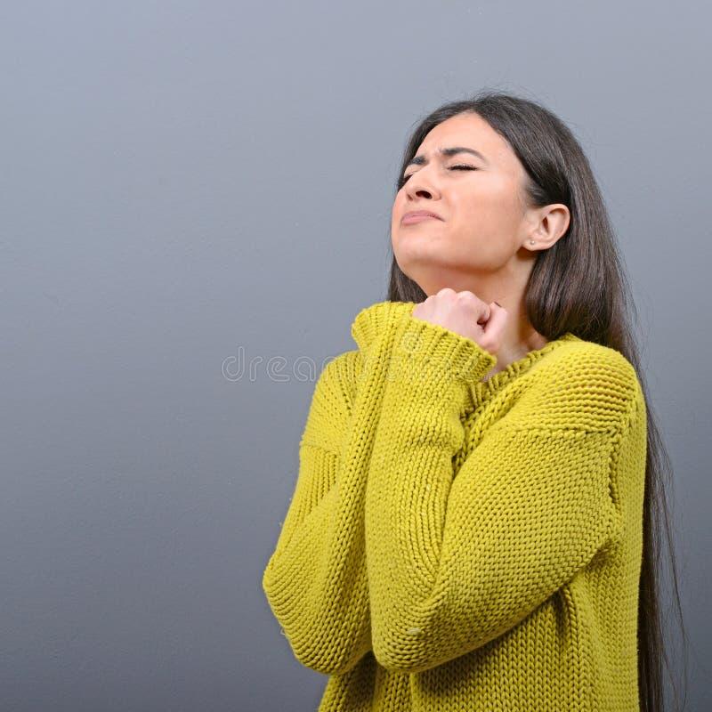 Mulher que reza sobre algo ou que implora pela mercê contra o fundo cinzento imagem de stock royalty free