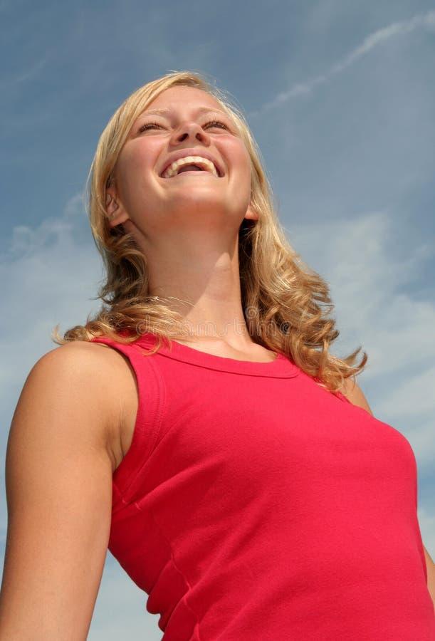 Mulher que ri de encontro ao céu azul imagens de stock