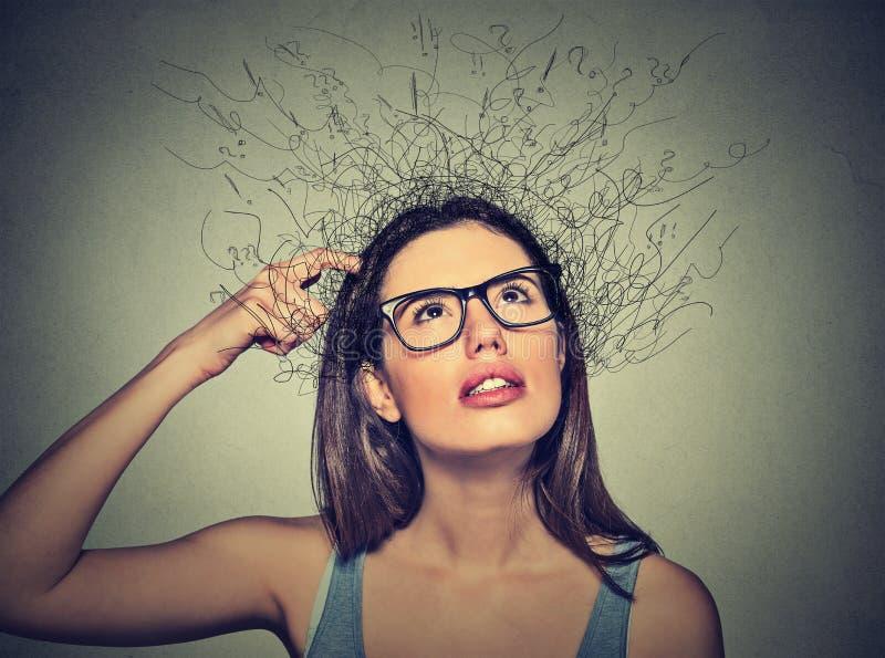 Mulher que risca a cabeça, pensando com o cérebro que derrete em linhas pontos de interrogação fotografia de stock royalty free