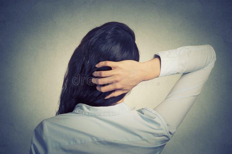 Mulher que risca a cabeça, vista traseira, pensamento, fazendo a decisão imagem de stock